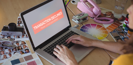 Transaction declined text on display against graphic designer working on laptop at creative office