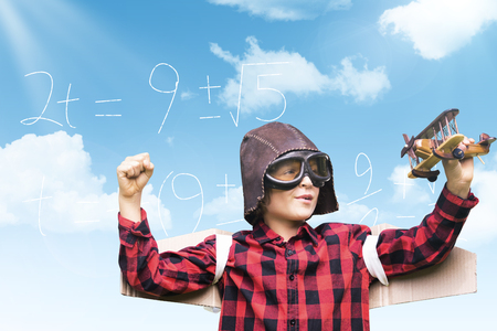 Boy in aviator cap holding toy airplane against blue sky Stock Photo