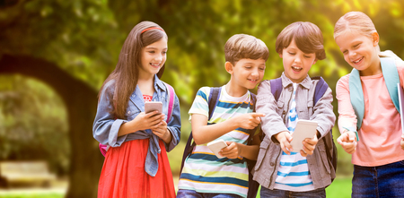 Boy with friends using mobile phone against trees and meadow in the park Stock Photo