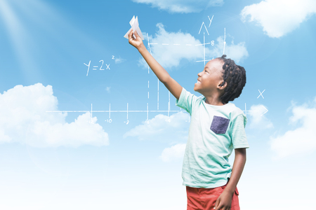 Child holding paper airplane against blue sky