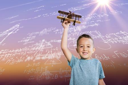 Portrait of boy holding toy airplane against sunrise sky