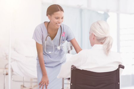 Smiling nurse assisting female patient in wheelchair against breast cancer awareness ribbon Stock Photo