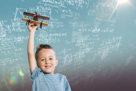 Portrait of boy holding wooden toy airplane against blue sky Stock Photo