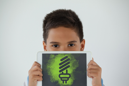 Digital composite image of light bulb on green spray paint against schoolboy holding digital tablet against white background Stock Photo
