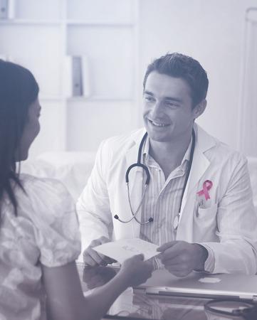 Borstkanker bewustzijn lint tegen lachende arts een recept te geven aan zijn vrouwelijke patiënt Stockfoto