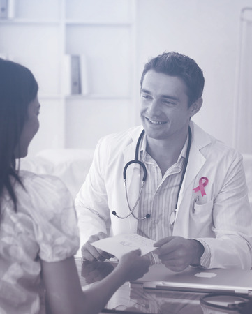 Breast cancer awareness ribbon against smiling doctor giving a prescription to his female patient
