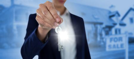 Sección media de empresaria mostrando la llave de la casa contra el exterior de la casa con césped verde