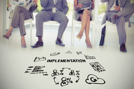 Implimentation text amidst several vector icons against business people sitting on chairs Stock Photo