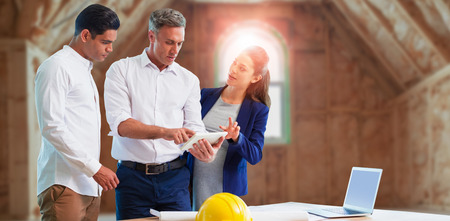 Architect discussing over tablet computer against room in house construction site