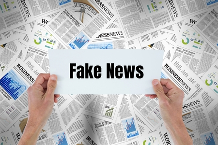 Digital composite of Hands holding card with Fake news against 3d newspapers Stock Photo
