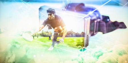 Rugby players training on pitch against virtual reality headset on table