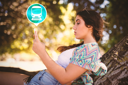 Digital composite image of train icon on green circle against side view of woman using phone Stock Photo