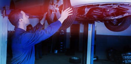 Auto mechanic examining car tire in garage