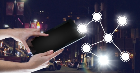 Digital composite of Hand holding tablet with icons interface of internet of things