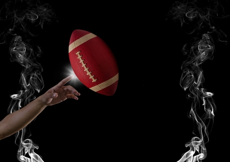 Digital composite of finger touching american football  in smoke