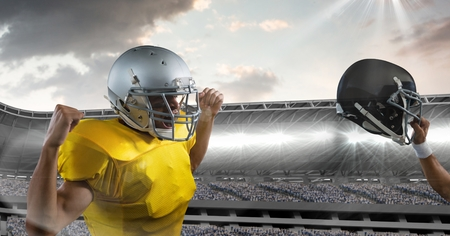 Digital composite of american football player cheering and holding up helmet Stock Photo