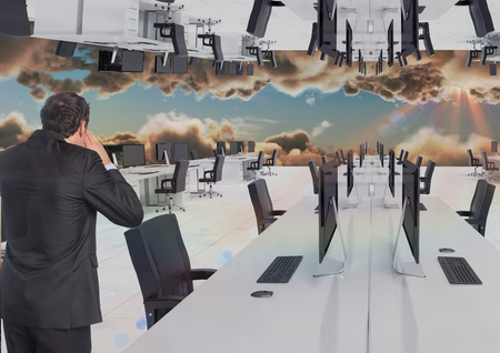 Digital composite of businessman standing in inverted office in the clouds