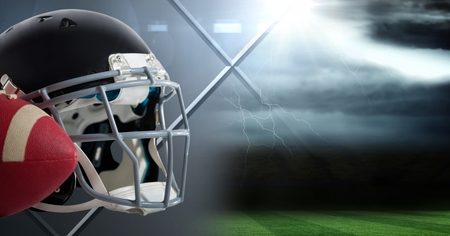 Digital composite of American football helmet and ball with field transition