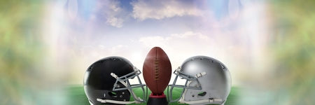 Digital composite of American football versus team helmets with ball with sky transition Stock Photo