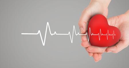 Digital composite of Heart beat over hands holding heart Reklamní fotografie
