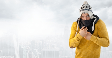 Digital composite of Man keeping warm in hat and scarf in bright city