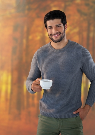 Digital composite of Man in Autumn with cup in forest