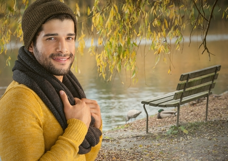 Digital composite of Man in Autumn with hat and scarf in park with pond