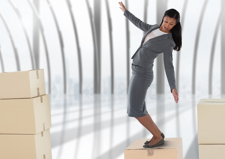 Digital composite of Businesswoman balancing on cardboard boxes by windows
