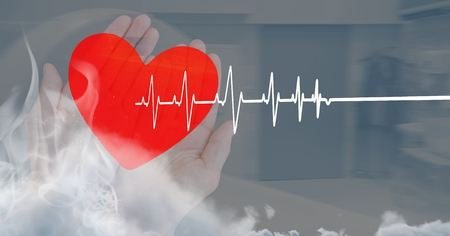 Digital composite of Heart beat over hands holding heart Stock Photo