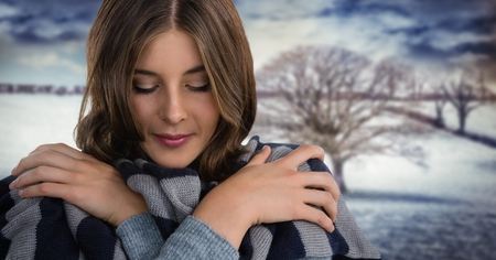 Digital composite of Woman wearing scarf keeping warm in snow landscape with bare tree Stock Photo