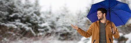 Digital composite of Man with blue umbrella in snow forest Stock Photo