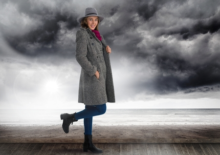 phoning: Digital composite of Woman in hat and warm clothes under dark clouds and sea