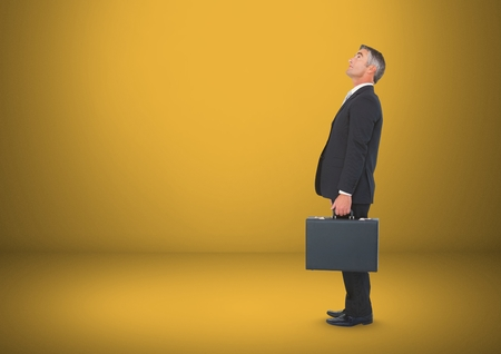 mature adult: Digital composite of businessman with briefcase in yellow room