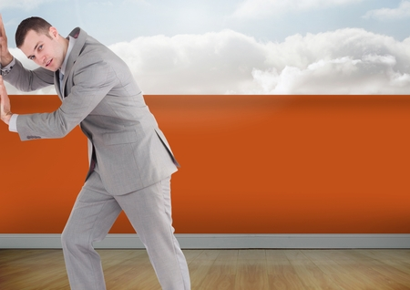 Digital composite of Businessman with orange wall pushing Stock Photo