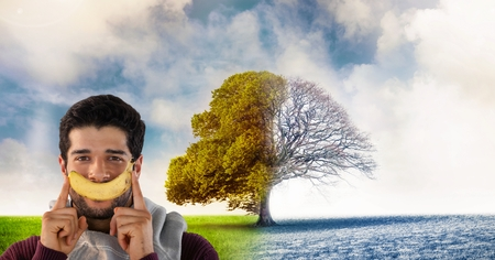 Digital composite of Man in Autumn and Winter transition with banana smile seasonal tree Stock Photo