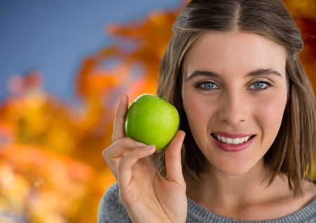 Digital composite of Woman in Autumn with apple in front of orange leaves