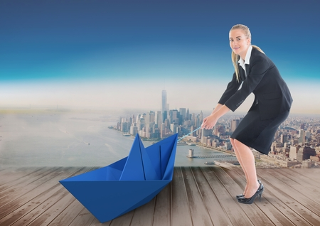 Digital composite of Businesswoman pulling paper boat with rope in city sky