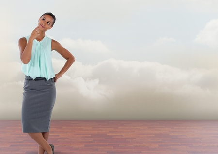 Digital composite of Businesswoman thinking with clouds