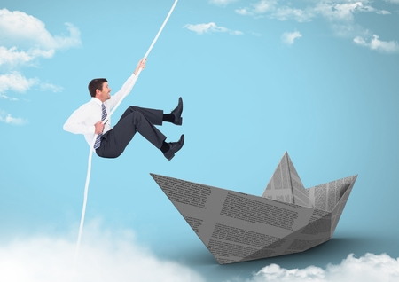 Digital composite of Businesman swinging on rope with paper boat in sky Stock Photo