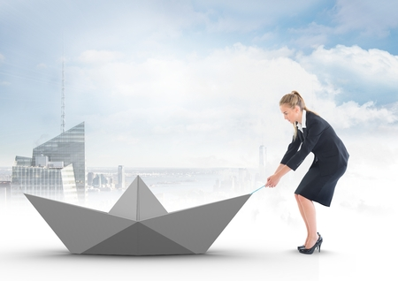 tied in: Digital composite of Businesswoman pulling paper boat with rope in city sky