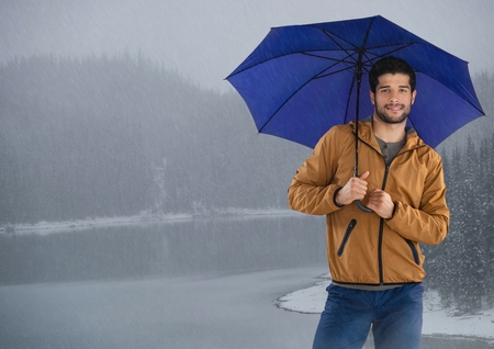Digital composite of Man with umbrella over icy lake Stock Photo