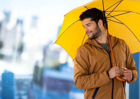 Digital composite of Man with yellow umbrella and blurred blue background Stock Photo