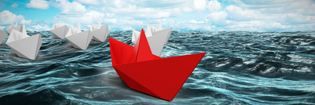 Red and white paper boats made of origami against waves in sea against cloudy sky