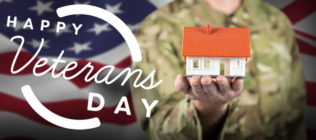 Mid section of soldier holding model house against focus on usa flag