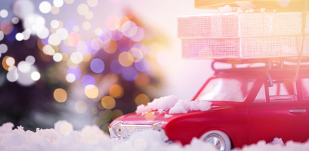 Toy car carrying christmas present on fake snow during christmas time