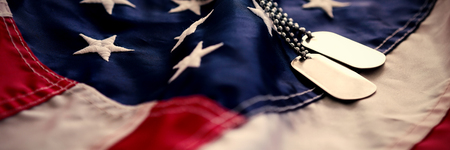 縞模様のアメリカ国旗の上のドッグタグチェーン 写真素材