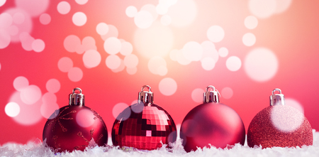 Various type of Christmas baubles lined up on snow against red background