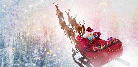 Hoge hoekmening van Santa Claus die op slee met giftdoos berijden tegen sneeuwpijnboombomen op de helling van de alpberg
