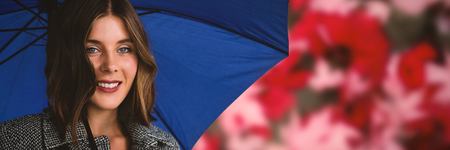 Close up portrait of woman with blue umbrella against maple leaves fallen on road