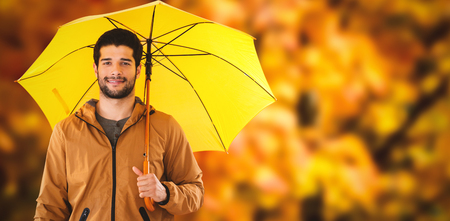 Portrait of young man holding yellow umbrella against low angle view of maple leaves Stock Photo